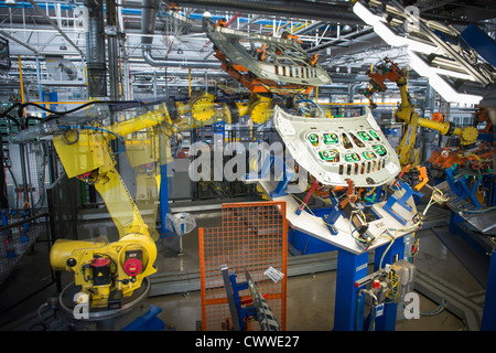 Robots handling car parts in car factory - Stock Photo