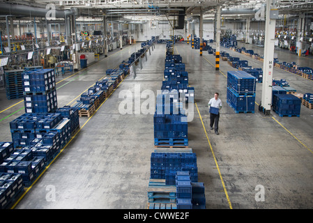 Worker selecting car parts in car factory - Stock Photo
