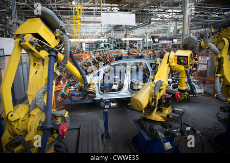 Robots welding car body in car factory - Stock Photo