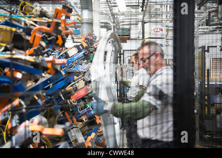 Workers handling car parts in car factory - Stock Photo