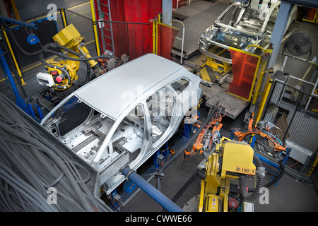 Car body with robots on production line in car factory - Stock Photo