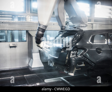 Paint spraying robots in car factory - Stock Photo