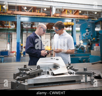 Engineers discussing car parts in car factory - Stock Photo