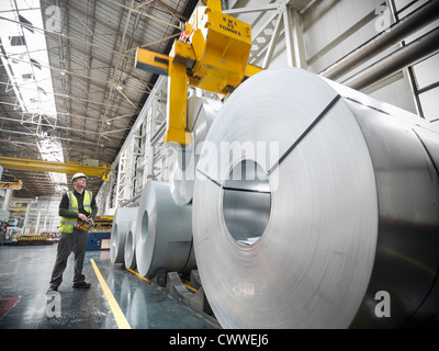 Worker operating crane with steel rolls in car factory - Stock Photo