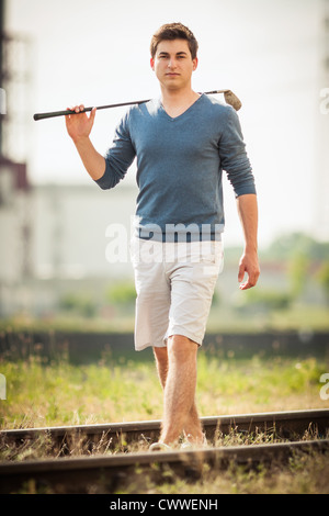 Man carrying golf club on tracks - Stock Photo