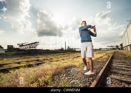 Man playing golf on train tracks - Stock Photo