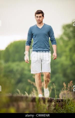 Man walking on train tracks - Stock Photo