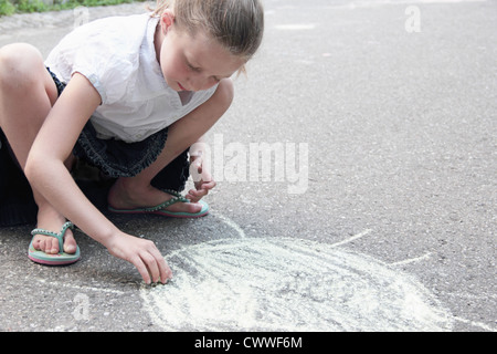 Girl drawing sun on sidewalk in chalk - Stock Photo