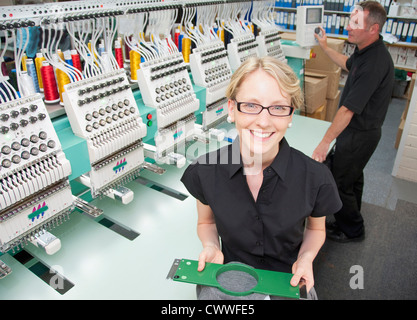Worker examining fabric in factory - Stock Photo