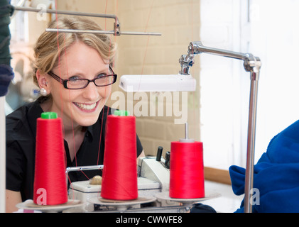 Worker sewing fabric in garment factory - Stock Photo