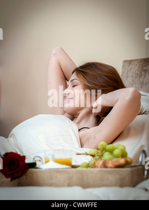 Woman waking up to breakfast in bed - Stock Photo