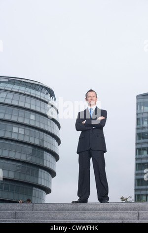 Businessman standing on urban steps - Stock Photo