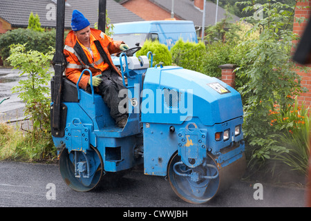 construction worker on a utility roller laying new tarmac driveway in the uk - Stock Photo