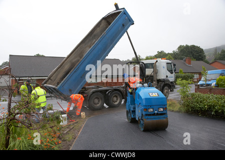 construction crew laying new tarmac driveway in the uk - Stock Photo