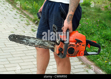 Woodworker with chain saw going to work - Stock Photo