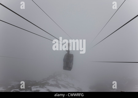 Ski lift on wires in fog - Stock Photo