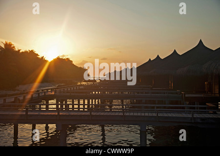 Sun setting over wooden docks on water - Stock Photo