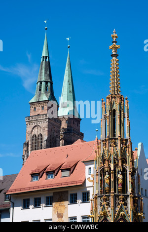 Schoene Brunnen (Beautiful Fountain) and spires of St Sebald's church in Nuremberg in Bavaria Germany - Stock Photo