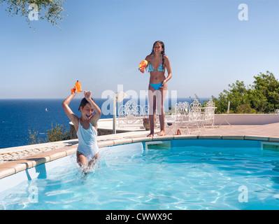 Teenage girls playing in swimming pool - Stock Photo