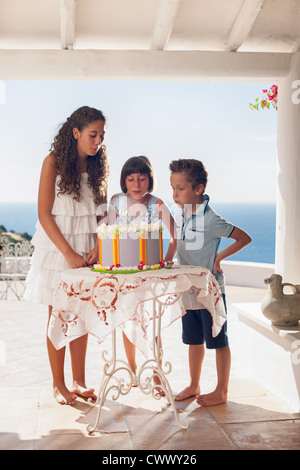 Children blowing out birthday candles - Stock Photo
