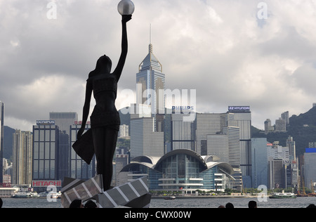 'Hong Kong Film Awards' statue (woman holding a ball) with the skyline of Hong Kong in the background (Hong Kong, - Stock Photo