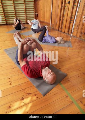 Older people practicing yoga in studio - Stock Photo