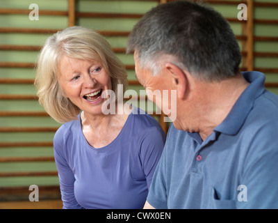 Older couple talking in gym - Stock Photo
