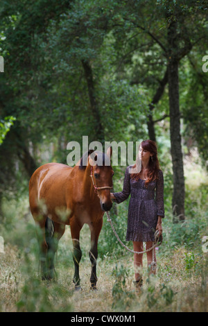 Woman walking horse in forest - Stock Photo