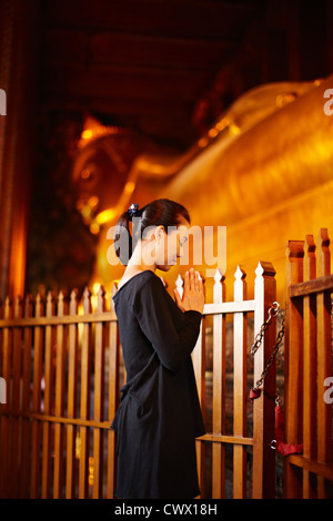 Woman praying at monument outdoors - Stock Photo