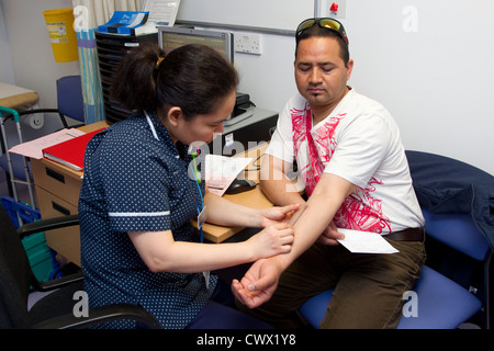 Nurse measuring scab for positive result of Tuberculosis test - Stock Photo