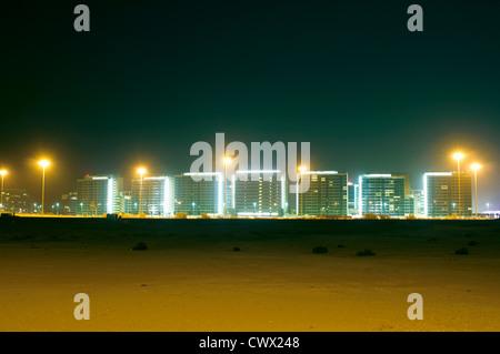 Urban skyline lit up at night - Stock Photo