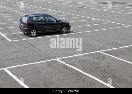 A single car parked on a large parking lot, concept image, parking spaces in Germany, Europe - Stock Photo