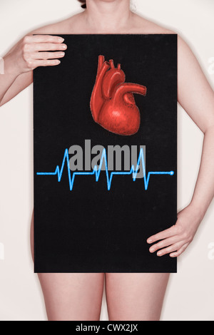 Woman holding a blackboard with an illustration of a human heart and an ECG pulse drawn on it in chalk. Concept - Stock Photo