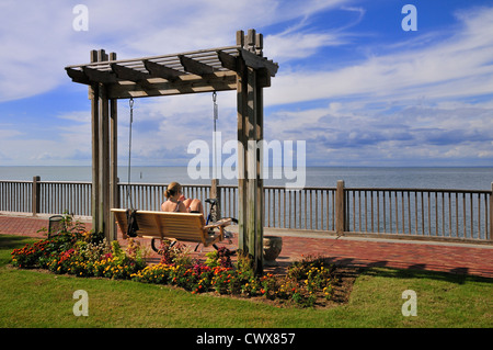 A bicyclist rests on a hanging bench near the Grand Hotel at Point Clear, Alabama - Stock Photo