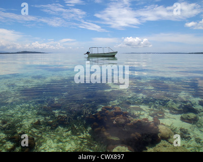 Boat over a shallow coral reef in calm waters of the Caribbean sea - Stock Photo