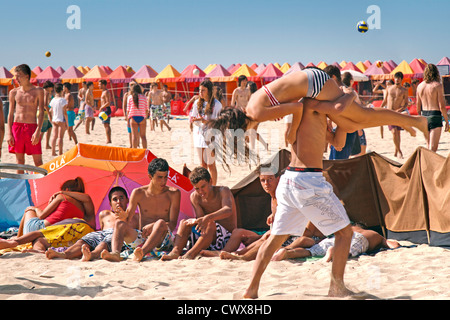 Teenagers having fun in the sun on the beach  - a girl being carried over the shoulder of a young man others playing - Stock Photo