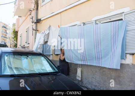 An elderly woman hangs a shot of clean clothes in front of a house in Corfu town, Corfu, Ionian Islands, Greece. - Stock Photo
