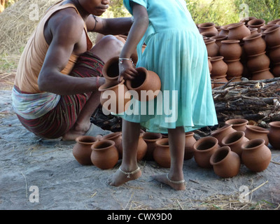 ORISSA, INDIA - Nov 13 -Potter builds an outdoor kiln for clay pots on Nov 13, 2009, in Orissa, India - Stock Photo