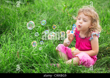 Little girl blowing bubbles in the grass. - Stock Photo