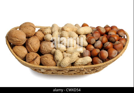 Walnuts, hazelnuts and peanuts in a wicker basket on a white background, isolated - Stock Photo