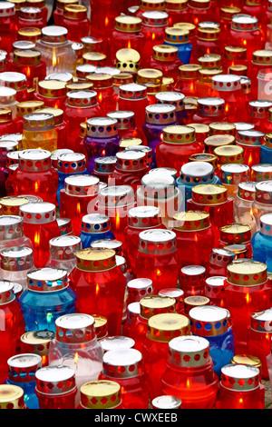 A lot of illuminated votive candles glows on a grave, lantern - Stock Photo