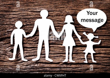 Cardboard figures of the family on a wooden table. The symbol of unity and happiness. Above the daughter bubble, - Stock Photo