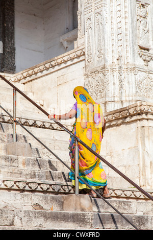 India lady in colorful traditional sari on steps at the entrance of Shree Jagat Sheromani Ji Hindu temple temple - Stock Photo