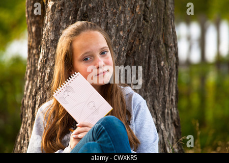 Teen-girl shows notebook while sitting in the park (looks into the camera) - Stock Photo