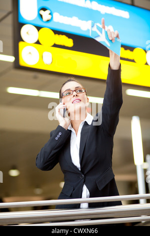 young businesswoman waving to someone while talking on cell phone at airport - Stock Photo
