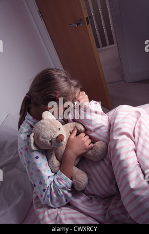Young girl in bed cuddling a teddy bear. - Stock Photo