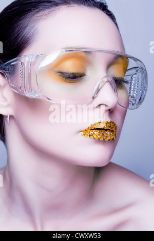 Young caucasian woman with gold fashion makeup wearing clear glasses and gold diamonties on her lips - Stock Photo