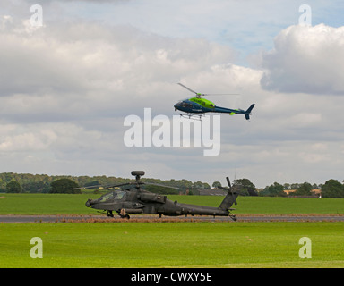AS 355N Twin Squirrel helicopter flying over an RAF Military Apache AH-64 Attack Helicopter.  SCO 8381 - Stock Photo
