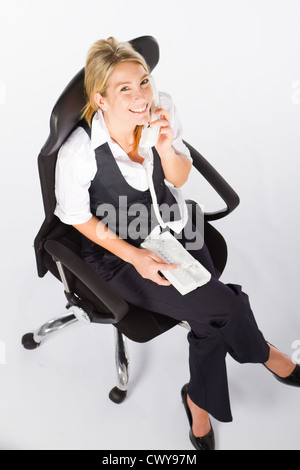 overhead view of young businesswoman sitting on office chair and talking on the phone - Stock Photo