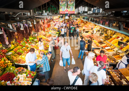 Indoor grocery market in Barcelona, Spain. People walking and buying food. Huge variety of fruits, vegetables and - Stock Photo